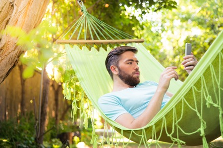 young girl: Handsome man lying on hammok and using smartphone outdoors