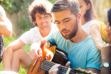 Group of a students with guitar resting outdoors