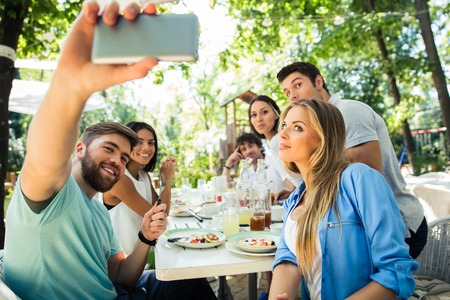 making fun: Portrait of a friends making selfie photo on smartphone in outdoor restaurant
