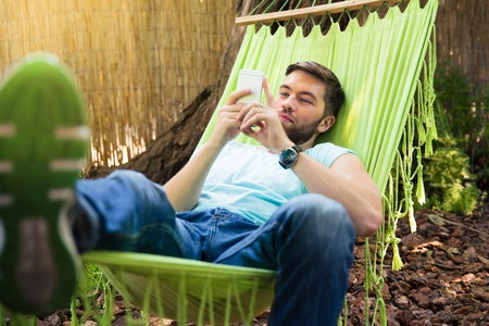 people relax: Young man lying on hammok and using smartphone outdoors