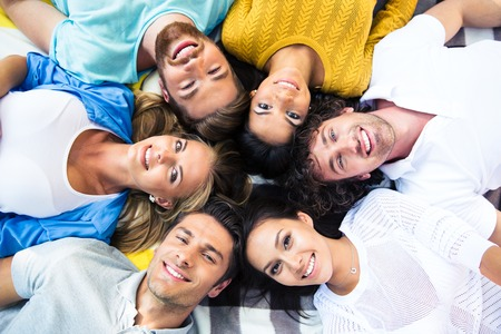 sociable: Group of cheerful friends lying together in a circle Stock Photo
