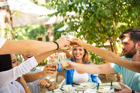 proposing a toast: Group of a smiling friends making toast around table at dinner party in outdoor restaurant