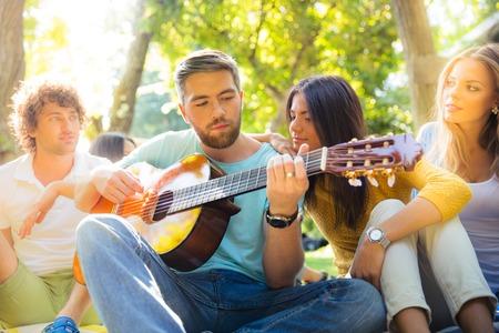 joy: Young friends with guitar having fun outdoors
