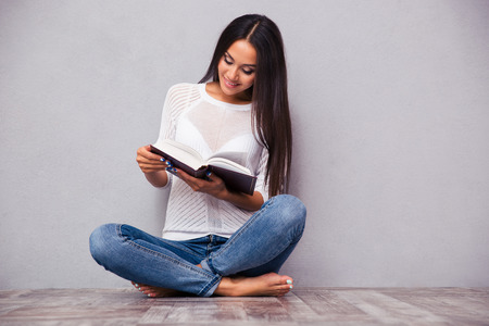 the caucasian beauty: Portrait of a smiling girl sitting on the floor and reading book on gray background Stock Photo