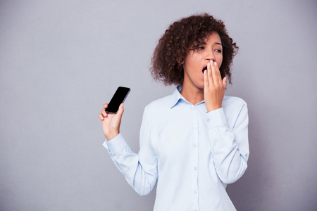 sleepiness: Portrait of afro american woman yawning while holding smartphone on gray background Stock Photo
