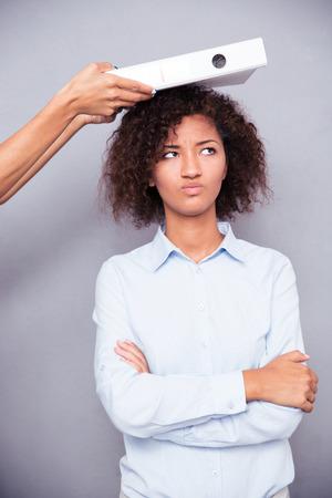 cara triste: Foto del concepto de la mujer americana afro ofendido stnading con los brazos cruzados sobre fondo gris Foto de archivo