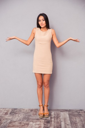 hysterics: Full length portrait of a young attractive woman shrugging shoulders on gray background