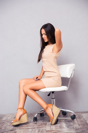 backpain: Portrait of a young woman sitting on office chair with backpain on gray background