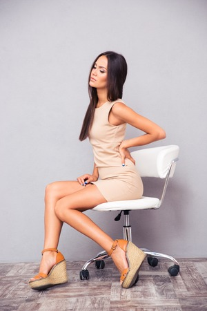 backpain: Portrait of elegant woman sitting on office chair with backpain on gray background Stock Photo
