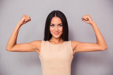 attitude: Retrato de una mujer elegante feliz mostrando su bíceps sobre fondo gris