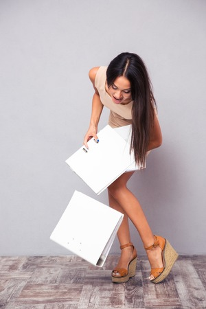 multiples: Businesswoman dropping folders on the floor over gray background Stock Photo