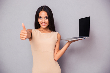 browsing: Happy woman holding laptop and showing thumb up over gray background. Looking at camera Stock Photo