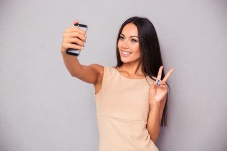 making dresses: Portrait of a smiling woman making selfie photo on smartphone over gray background