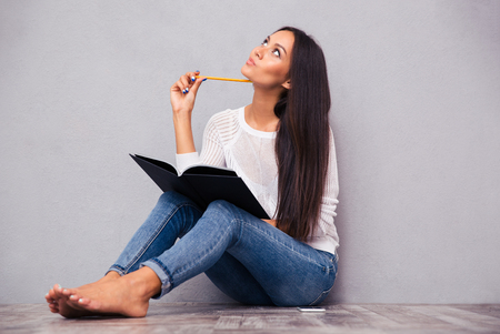 women: Portrait of a pensive girl sitting on the floor with notepad and pencil on gray background Stock Photo