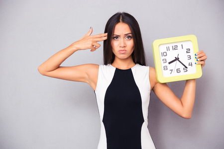 holding gun to head: Tired woman holding clock and showing gun gesture to her head over gray background
