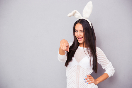 Portrait of a happy woman in bunny ears winking and pointing finger at camera over grya background Stock Photo