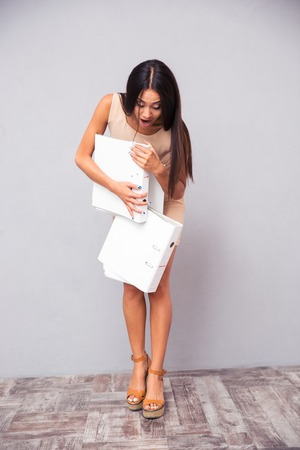 overloading: Businesswoman dropping folders on the floor over gray background Stock Photo
