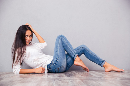 Portrait of a smiling attractive woman lying on the floor on gray background Stock Photo