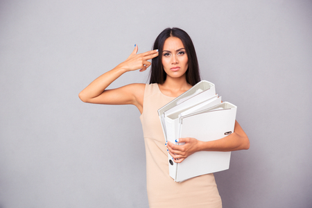 holding gun to head: Businesswoman holding folders and making gun gesture to her head over gray background Stock Photo