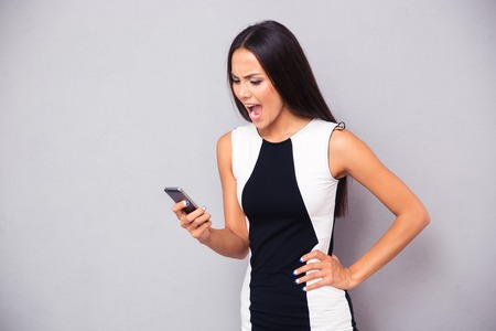angry person: Angry woman in dress shouting on smartphone over gray background Stock Photo
