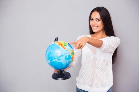Portret van een lachende jonge vrouw wijzende vinger op bol op een grijze achtergrond Stockfoto - 44557934