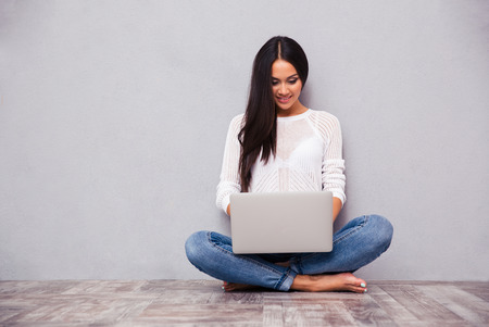 wireless woman work working: Portrait of a happy casual woman sitting on the floor with laptop on gray background