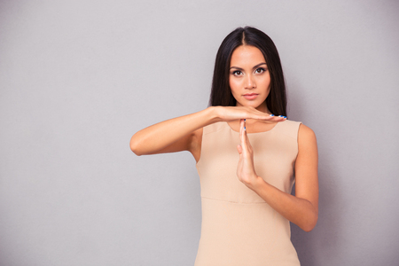 restrain: Beautiful woman showing time out sign over gray background