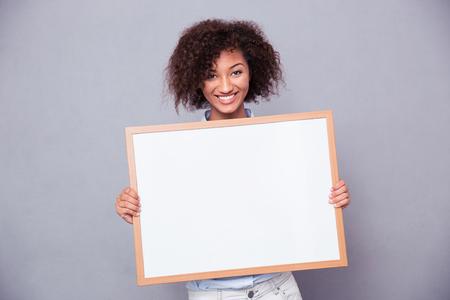Portrét usměvavý afro americká žena hospodářství prázdné palubě více než šedé pozadí