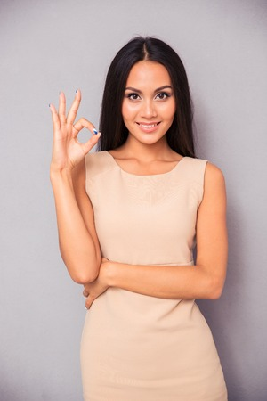 likable: Smiling woman making ok sign with fingers over gray background