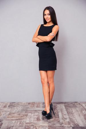 腕を組んで灰色の背景に立っている若い実業家の完全な長さの肖像画 写真素材