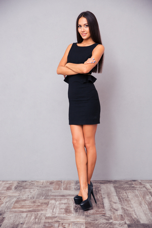 Full length portrait of a young businesswoman standing with arms folded on gray background