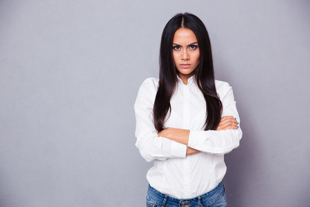 annoyed: Portrait of angry woman standing with arms folded on gray background Stock Photo