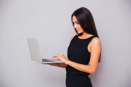 woman in dress: Portrait of a beautiful businesswoman using laptop on gray background