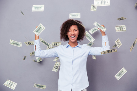 Concept photo of a cheerful afro american woman standing under rain with money on gray background