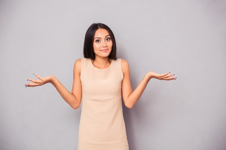 'head and shoulders': Portrait of a young woman shrugging shoulders over gray background Stock Photo