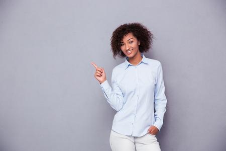 Portret van een glimlachende Afro-Amerikaanse zakenvrouw wijzende vinger weg over grijze achtergrond en kijken naar de camera