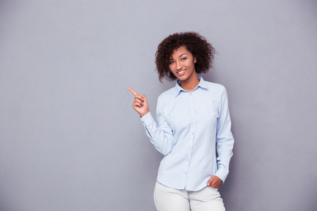 dedo apuntando: Retrato de un dedo americano afro sonriente de negocios que señala lejos sobre fondo gris y mirando a la cámara Foto de archivo