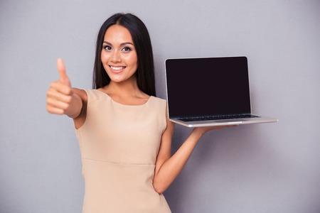 노트북을 들고 회색 배경 위에 엄지 손가락을 보여주는 쾌활 한 여자의 초상화. 카메라를 보면서 스톡 콘텐츠