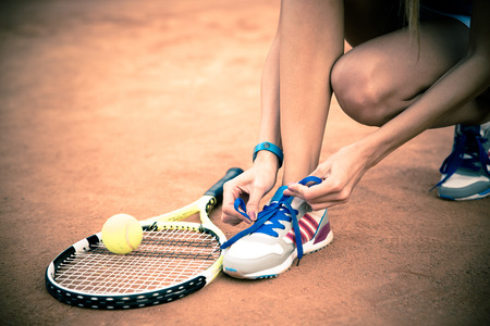 woman close up: Tennis player tying shoelaces outdoors Stock Photo