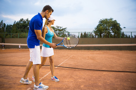 Portrait of a man training woman to play tennis outdoors