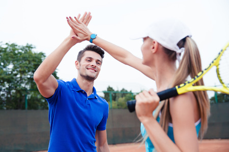 Male and female tennis players gives five at the tennis court after a match