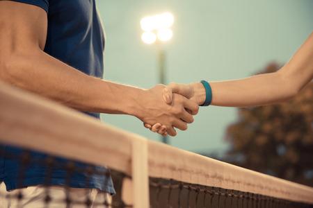 saludo de manos: Retrato de detalle de un apretón de manos del hombre y la mujer en la pista de tenis después de un partido Foto de archivo