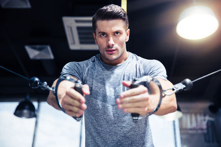 a workout: Portrait of a man workout on fitness machine in gym Stock Photo