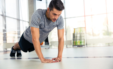 musculine: Portrait of a sportss man doing push-ups in gym Stock Photo