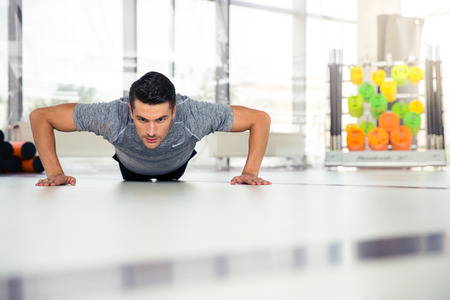 musculine: Portrait of a fitness man doing push-ups at gym