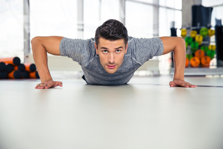 musculine: Portrait of a handsome man doing push-ups in gym