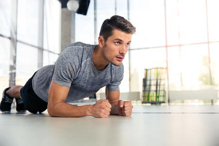 motion: Porträtt av en fitness man gör bordläggning övning i gymmet