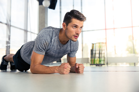 exercises: Portrait of a fitness man doing planking exercise in gym Stock Photo