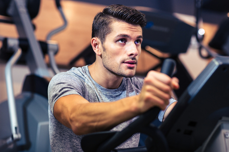 1: Portrait of a handsome man workout on a fitness machine at gym