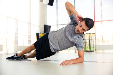 Portrait of a handsome man doing side plank at gym Foto de archivo